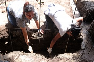 Sandra the home owner and Brit from HFH both step in to work the concrete spreading in the trenches